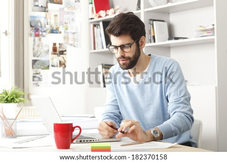 Young small business owner sitting at desk and working at home. - stock photo