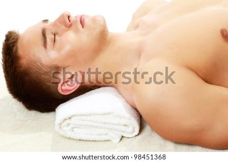 Young smart male enjoying massage - stock photo