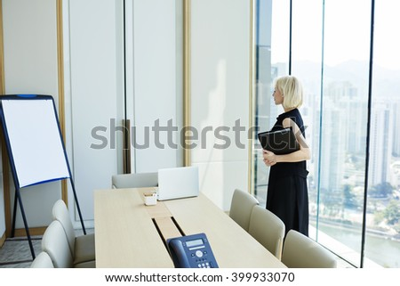Young smart woman managing director with paper documents is hand is reading a business plan that she prepared for investors on flip chart with copy space for your advertising text message or content - stock photo