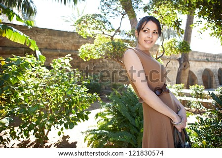 Young smart woman visiting a touristic sight's garden while on vacation during a sunny day. - stock photo