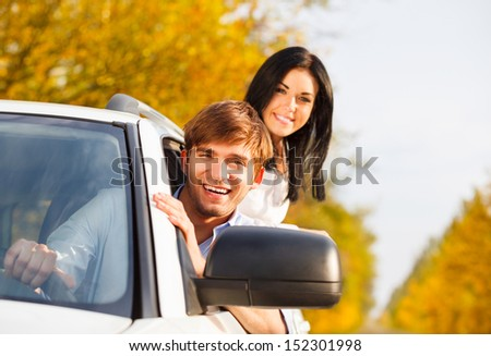 young smile couple driving car, fall season, golden autumn trees, yellow leaves background