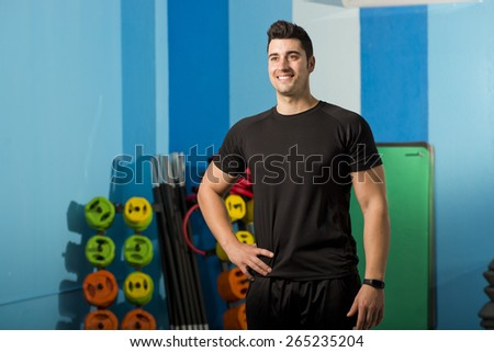 Young smile fit attractive man posing in gym - stock photo