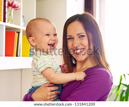 young smiley mother and adorable son at home