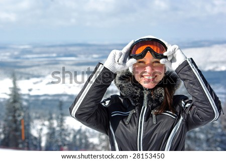 Young smiley woman in ski sunglasses over mountains landscape - stock photo