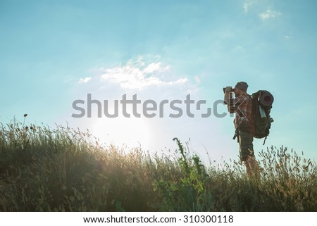 Young smilimg caucasian tourist with backpack  standing on the top of hill against blue sky background and looking through binoculars - stock photo