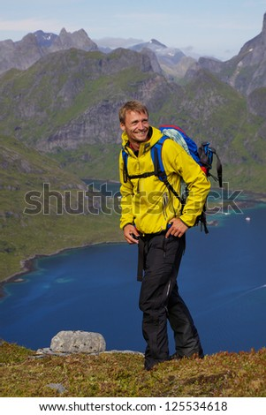 Young smiling active man with backpack hiking on Lofoten islands in Norway on sunny day high above fjord
