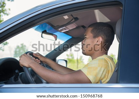 Young Smiling African American Male Driving a Car - stock photo