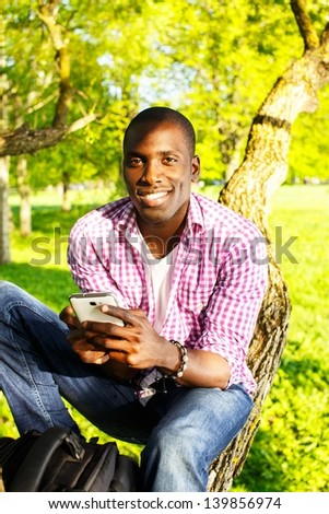Young smiling african american sitting on a tree in park  with mobile phone - stock photo