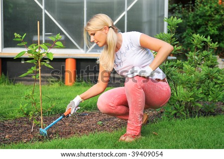 Young smiling attractive blond girl working in the garden near the greenhouse - stock photo