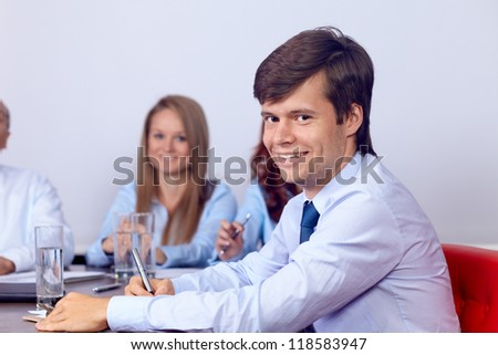 Young smiling attractive businesswoman sitting on a business meeting with colleagues, background in the office