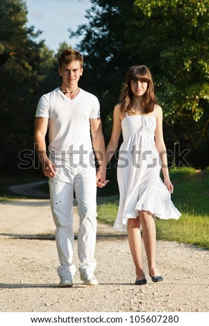 Young smiling attractive couple walking in park - stock photo