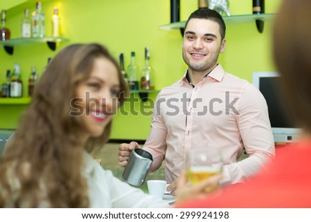 Young smiling bartender and smiling women with wine at bar. Focus on man - stock photo
