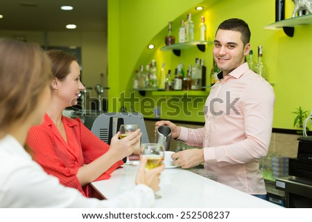 Young smiling bartender and two beautiful girls with wine glasses in hands at bar. Focus on man