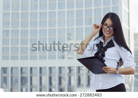 Young smiling beautiful elegant business woman brunette in white blouse and glasses with black folder on background skyscraper. Success concept.