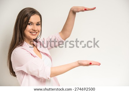 Young smiling beautiful girl showing copy space over grey background. - stock photo