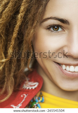 Young smiling beautiful woman with dreadlocks in red clothes closeup. - stock photo