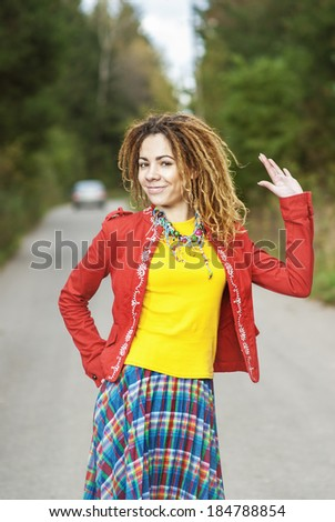 Young smiling beautiful woman with dreadlocks in red clothes on an asphalt road. - stock photo