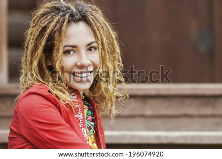 Young smiling beautiful woman with dreadlocks in red dress sitting on wooden bench. - stock photo