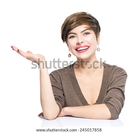 Young smiling beauty woman with bob showing empty copy space on the open hand palm on white background. Happy girl presenting point by raised hand for text. Gesture for selling product, advertisement. - stock photo