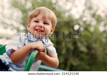 Young Smiling Blond Boy Sitting Outdoors on Playground with Copyspace - stock photo