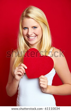 young smiling blond woman with a heart in her hands - stock photo