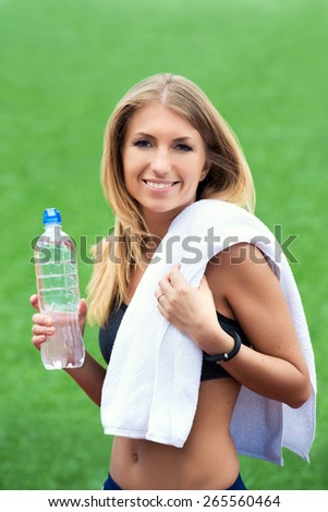 Young smiling blond woman with towel and water bottle after a workout on a background of green grass