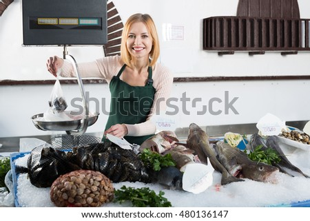 Young  smiling blonde shopgirl near scales and display with fish