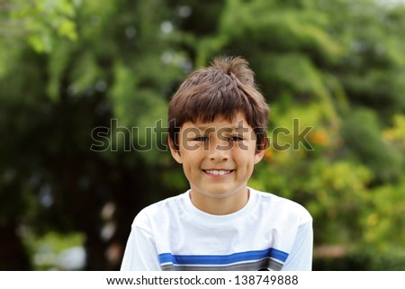 Young smiling boy in a park with white tee shirt