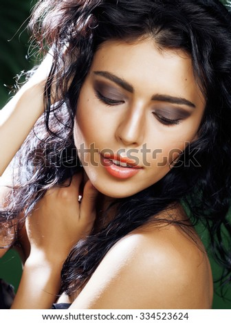 young smiling brunette woman on green background close up, exotic view asian vacation - stock photo