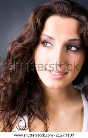 Young smiling brunette woman portrait. On dark background.
