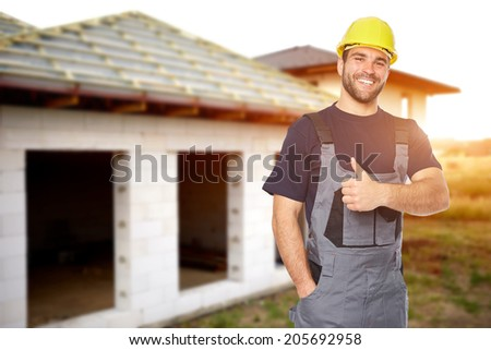 Young smiling builder gesture with his thumb up in front of the building. Toned - stock photo