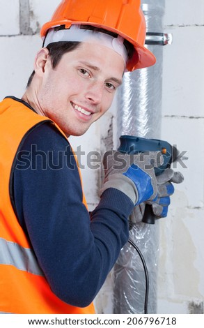 Young smiling builder with drill in hands, vertical