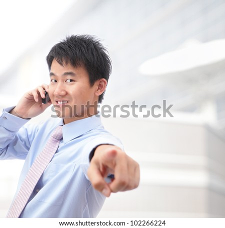 Young smiling business man calling on mobile phone at office, model is a asian - stock photo