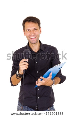 young smiling business man with notes announcing on microphone - stock photo