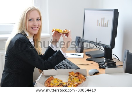 Young smiling business person on work place eating pizza
