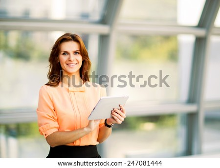 Young smiling business woman holding digital tablet computer - stock photo