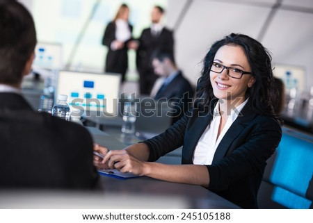 Young smiling business woman is looking at the camera during presentation in modern conference hall. - stock photo