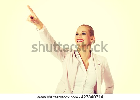 Young smiling business woman pointing for copyspace or something - stock photo