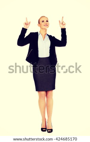 Young smiling business woman pointing up - stock photo