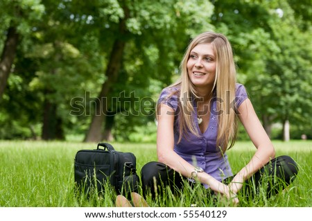 Young smiling business woman siting in grass and relaxing after work