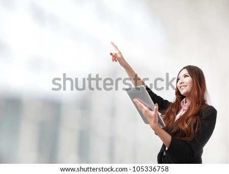 Young smiling business woman using tablet computer and hand finger point to empty copy space, model is a asian beauty - stock photo