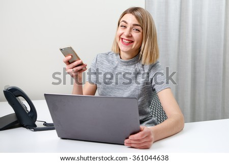Young smiling business woman with mobile phone sitting at her workplace in office