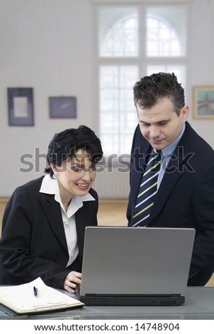 Young smiling businessman and a businesswoman working together with a laptop