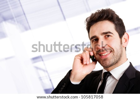 Young smiling businessman calling on phone at office - stock photo