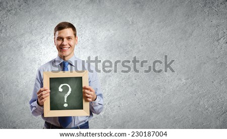Young smiling businessman holding chalkboard with question sign - stock photo