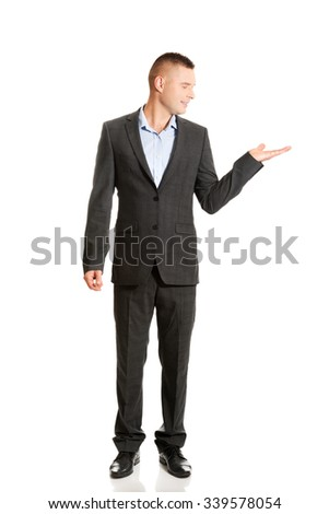 Young smiling businessman holding copyspace. - stock photo
