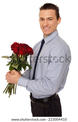 Young smiling businessman holds bouquet of beauty red roses