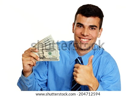 Young smiling businessman in blue shirt shows you money with thumb up - stock photo