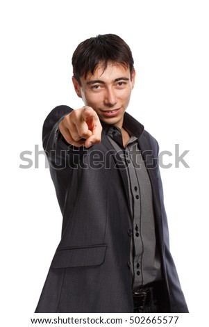 Young smiling businessman in dark grey lounge suit with short brunet hair standing with finger pointing gesture isolated on white background