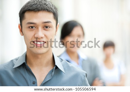 Young smiling businessman looking at camera with his colleagues behind